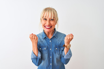Middle age woman wearing casual denim shirt standing over isolated white background celebrating surprised and amazed for success with arms raised and open eyes. Winner concept.