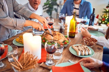 Beautiful family meeting smiling happy and confident. Carving roasted turkey celebrating Christmas at home