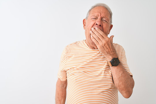Senior grey-haired man wearing striped t-shirt standing over isolated white background bored yawning tired covering mouth with hand. Restless and sleepiness.
