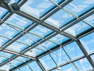 closeup inside view of modern transparent glass roof. blue sky through a glass ceiling