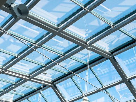 closeup inside view of modern transparent glass roof. blue sky through a glass ceiling