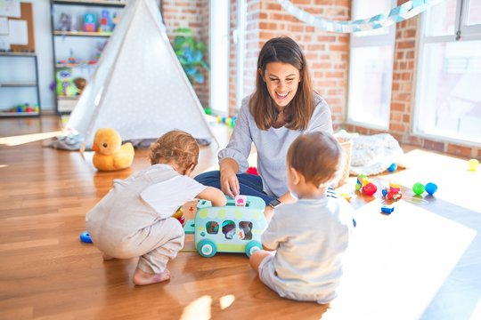 Beautiful teacher and toddlers playing around lots of toys at kindergarten