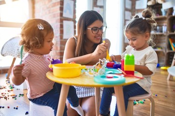 Young beautiful teacher and toddlers playing meals using plastic food and cutlery toy at...