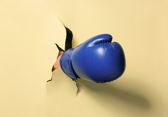 Hand in boxing glove tearing color paper