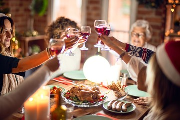 Beautiful group of women smiling happy and confident. Eating roasted turkey and toasting with cup of wine celebrating christmas at home