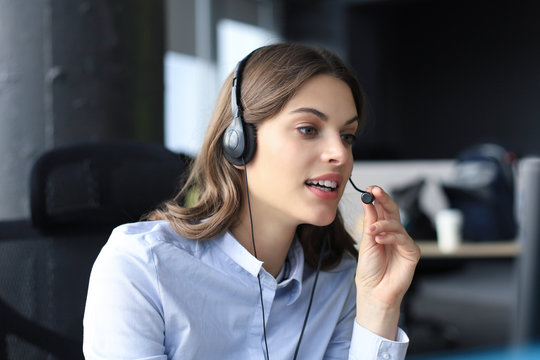 Beautiful smiling call center worker in headphones is working at modern office
