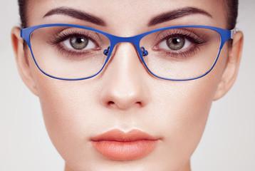 Female eye with long eyelashes in eyeglasses. Model in glasses. Vision correction. Poor eyesight. Spectacle frame. Makeup, cosmetics, beauty. Close up, macro
