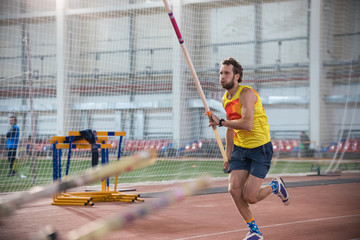 Obraz Pole vaulting - man in blue shorts is running with pole in hands - fototapety do salonu