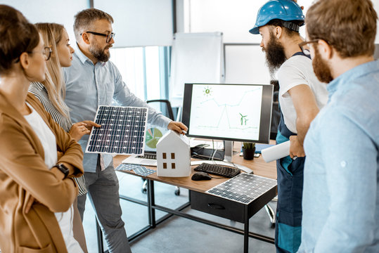 Group of alternative energy engineers discussing a project with a worker during a meeting in the office. Green energy development concept