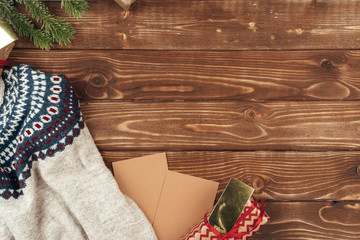 Warm sweater and Christmas gift on wooden background