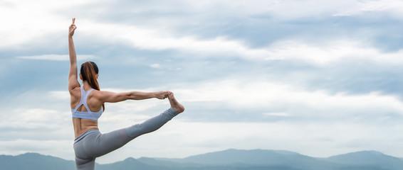 Yoga woman workout on the lake.