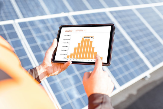 Workman examining genaration of solar power plant, holding digital tablet with a chart of electricity production. Concept of online monitoring of the electric station