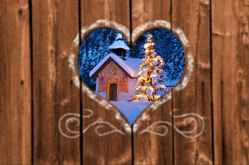 Looking through a carved heart in a wooden wall to a romantic and illuminated Christmas chapel