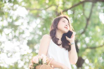 Asian women talking cellphone in city public park