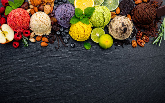 Various of ice cream flavor ball blueberry ,lime ,pistachio ,almond ,orange ,chocolate and vanilla set up on dark stone background . Summer and Sweet menu concept.
