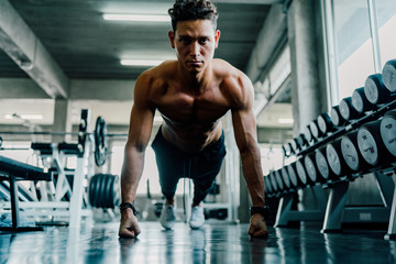 Young man doing Push ups in a gym. Fitness People Exercising at Gym.
