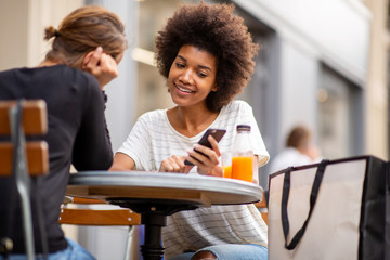 two young woman sitting at outdoor cafe together and looking at mobile phone