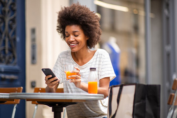 beautiful young black woman sitting at outdoor cafe with cellphone and drink