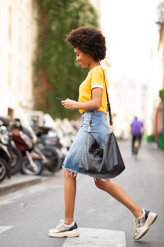 Full body side of young african american woman walking with cellphone on street