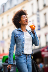 happy young black woman walking in city with shopping bag and drink