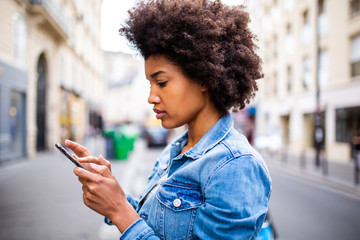 Side of young black woman with afro hair sending text message on cellphone