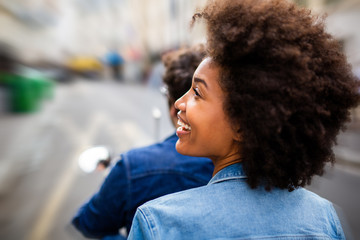 Close up of beautiful young african american woman riding as passenger on back of scooter