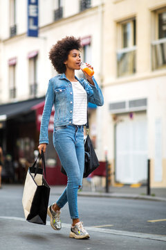 Full body of happy young woman walking in city with shopping bag and drink