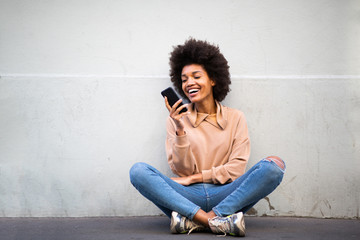 happy young african american woman sitting on floor with cellphone Fotobehang