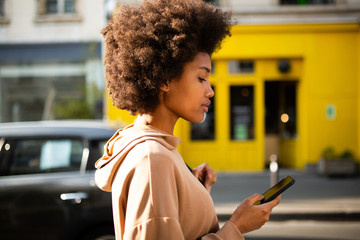 Side of beautiful young black woman with afro hairstyle walking with cellphone in city