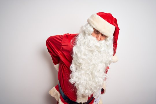 Middle age handsome man wearing Santa costume standing over isolated white background Suffering of backache, touching back with hand, muscular pain