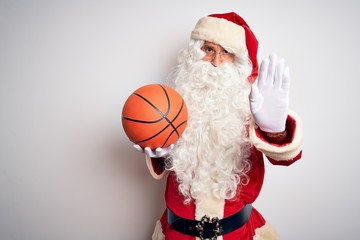 Senior man wearing Santa Claus costume holding basketball ball over isolated white background with...