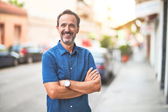 Middle age handsome man standing on the street smiling