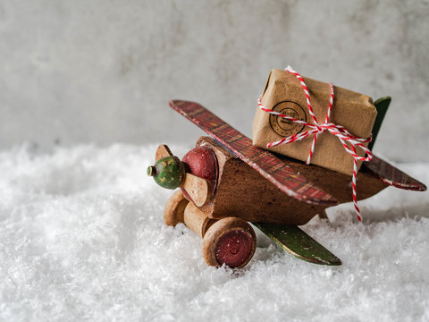 Christmas composition with a wooden vintage plane carrying a Christmas holiday gift