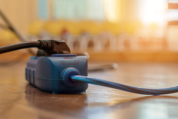 blue and black extension cord cable into power outlet indoors..