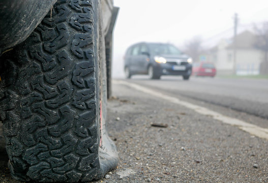 Flat off road tire on focus, moving cars on the blured background.