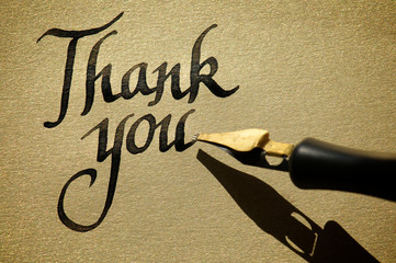 Thank you message handwritten in fresh black ink with old-fashioned calligraphy pen on textured gold paper