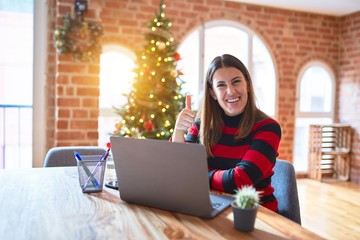 Beautiful woman sitting at the table working with laptop at home around christmas tree doing happy...