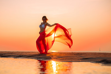 Woman posing with piece of clothing on the beach at sunset