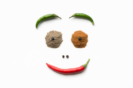 Smiley created from different kinds of pepper - red and green hot peppers, dried, black.