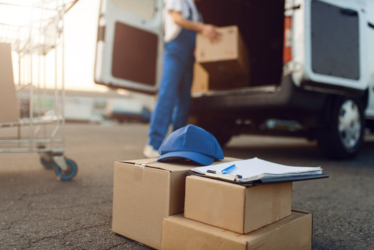 Parcel boxes and cap, deliveryman on background