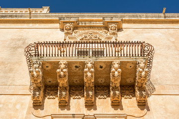 Beautiful ancient baroque balcony with horse ornaments in Noto, Sicily, Italy