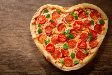 Valentines Day food. Heart shapped pepperoni pizza with green basil,  top view