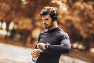 Keuken foto achterwand Jogging Portrait of young man on a morning jogging in the autumn park, man listening to music with headphones