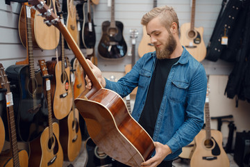 Tuinposter Muziekwinkel Bearded young man choosing a guitar in music store