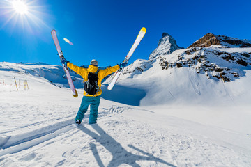 Wall Mural - Man skiing on fresh powder snow with Matterhorn in background, Zermatt in Swiss Alps.
