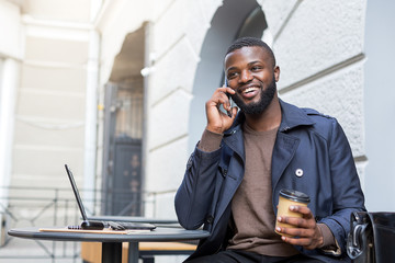 Happy entrepreneur talking with clients over the phone while holding a cup of coffee.