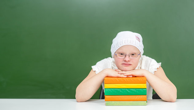 Portrait of a smart girl with Down Syndrome with books at school. Empty space for text