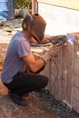 Welder welds fixture retainer during porch construction