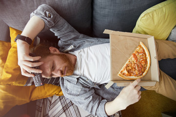 Above view portrait of bearded man lying on couch and eating pizza while watching TV at home, copy space
