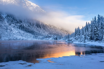 Winter sunrise over scenic frozen lake